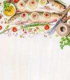 Frische Holzkohle mit Bestandteilen für die Fischgerichte, die auf weißem hölzernem Hintergrund, Draufsicht, Grenze kochen Stockbild