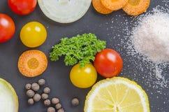 Frische köstliche Bestandteile für das gesunde Kochen oder Salat, der auf Hintergrund des dunklen Schwarzen macht Draufsicht, Fah Stockbilder
