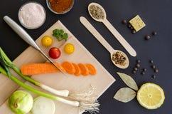 Frische köstliche Bestandteile für das gesunde Kochen oder Salat, der auf Hintergrund des dunklen Schwarzen und hölzernem Schneid Lizenzfreie Stockfotografie