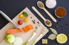Frische köstliche Bestandteile für das gesunde Kochen oder Salat, der auf Hintergrund des dunklen Schwarzen und hölzernem Schneid Stockfotos