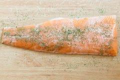 Frische köstliche Lachse mit den Petersilienkräutern lokalisiert auf einem Holztisch Stockfotografie