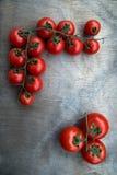 Frische köstliche Tomaten auf alter hölzerner Tischplatte Stockfotografie