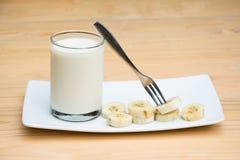 Frische kühle Milch und geschnittene Banane Stockfotos