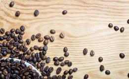 Frische Kaffeebohnen auf einem hölzernen Hintergrund für die Vorbereitung von Lizenzfreie Stockbilder