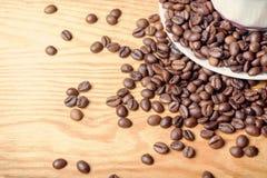 Frische Kaffeebohnen auf einem hölzernen Hintergrund für die Vorbereitung von Lizenzfreie Stockfotos