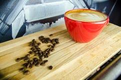 Frische Kaffeetasse mit Kaffeebohnen Stockfotos