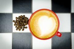 Frische Kaffeetasse mit Kaffeebohnen auf Kontrollbrett Lizenzfreies Stockbild