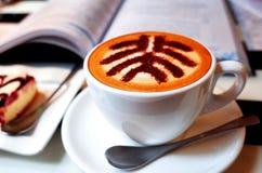 Frische Kaffeetassen und Kaffeebohnen herum Stockfoto