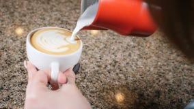 Frische Kaffeetassen und Kaffeebohnen herum Barista Prepares Coffee Vorbereitung von Latte Barista, das heiße Milch in einen Bech stock footage