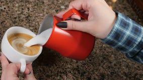 Frische Kaffeetassen und Kaffeebohnen herum Barista Prepares Coffee Vorbereitung von Latte Barista, das heiße Milch in einen Bech stock video