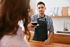 Frische Kaffeetassen und Kaffeebohnen herum Kaffee Barista Giving Cup Of zum Kunden lizenzfreies stockbild