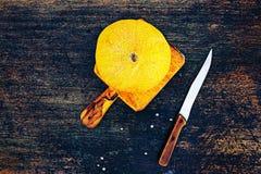 Frische Kantalupenmelone auf einem dunklen Hintergrund mit Messer Lizenzfreies Stockbild