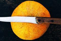 Frische Kantalupenmelone auf einem dunklen Hintergrund mit Messer Stockbild
