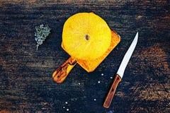 Frische Kantalupenmelone auf einem dunklen Hintergrund mit Messer und mose Flache Lageansicht des Landlebens Stockfotos