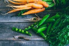 Frische Karotten mit grünen Oberteilen und Hülsen von Erbsen Lizenzfreie Stockbilder