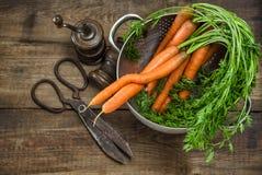 Frische Karotten mit Weinleseküchengeräten auf rustikalem hölzernem BAC Lizenzfreie Stockfotos