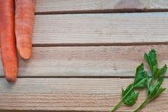 frische Karotten und Petersilie auf einem hölzernen Hintergrund Stockfotos