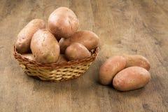 Frische Kartoffeln auf rustikalem hölzernem Hintergrund Lizenzfreie Stockfotos