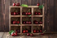 Frische Kirsche mit Wasser fällt auf rustikalen hölzernen Hintergrund Neuer Kirschhintergrund Gesundes Nahrungsmittelkonzept Stockfotografie