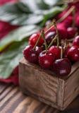 Frische Kirsche mit Wasser fällt auf rustikalen hölzernen Hintergrund Neuer Kirschhintergrund Gesundes Nahrungsmittelkonzept Stockbild