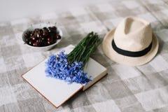 Frische Kirschen, Kornblumen, Strohhut und ein Buch auf dem Tisch Flache gelegte Tapete des Sommers, Draufsicht stockfotos