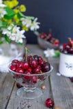 Frische Kirschfrucht im Glasvase, andere Teller mit Beeren und Glas mit Jasmin und Wildflowers auf dem alten Holztisch Weiches se Stockfotos