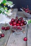 Frische Kirschfrucht im Glasvase, andere Teller mit Beeren und Glas mit Jasmin und Wildflowers auf dem alten Holztisch Weiches se Stockfoto