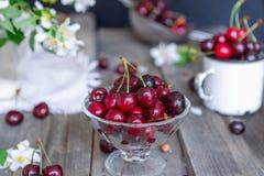 Frische Kirschfrucht im Glasvase, andere Teller mit Beeren und Glas mit Jasmin und Wildflowers auf dem alten Holztisch Weiches se Lizenzfreies Stockbild