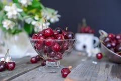 Frische Kirschfrucht im Glasvase, andere Teller mit Beeren und Glas mit Jasmin und Wildflowers auf dem alten Holztisch Weiches se Lizenzfreie Stockbilder