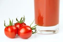 Frische Kirschtomaten und ein Glas voll vom Tomatensaft Stockfoto