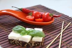 Frische Kirschtomaten und -paprika auf Rot Stockfotografie