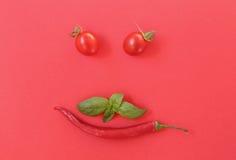 Frische Kirschtomaten und -paprika auf Rot Lizenzfreie Stockfotos