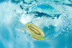 Frische Kiwi, die in Wasser fällt Lizenzfreies Stockfoto