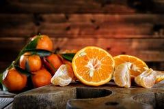 Frische Klementinen wählten frisch in den Scheiben und in den Keilen auf Holz aus stockfotos