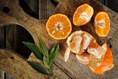 Frische Klementinen wählten frisch in den Scheiben und in den Keilen auf Holz aus lizenzfreies stockfoto
