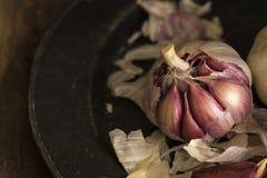 Frische Knoblauchzehen in der schwermütigen natürlichen Beleuchtung gründeten mit vintag Stockfoto