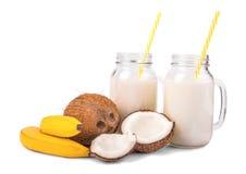 Frische Kokosnüsse, zwei geschmackvoll, helle gelbe Bananen und Weckglas zwei voll natürliche Kokosmilch lokalisiert auf einem we Stockfoto