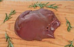 Frische Leber eines Schweins auf einem hölzernen Schneidebrett mit Niederlassungen des Rosmarins stockfotos