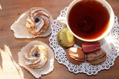 Frische Makronen mit Tee auf einem hellen Hintergrund stockfotografie