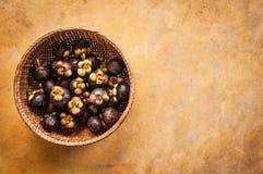 Frische Mangostanfrüchte im Strohkorb Lizenzfreies Stockfoto