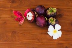 Frische Mangostanfrüchte mit Blume und Blättern auf hölzerner brauner Tabelle Stockfoto