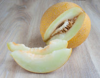 Frische Melone mit zwei Stücken auf einem beige Hintergrund Lizenzfreies Stockbild