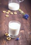 Frische Milch in und Glas auf hölzernem Hintergrund Milch im Glas und Lizenzfreie Stockbilder