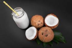 Frische Milch und vier organische Kokosnüsse knackten in halbem und in ganzem auf grünen Blättern und auf einem schwarzen Hinterg Lizenzfreies Stockbild