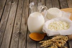 Frische Milchprodukte Milch und Hüttenkäse mit Weizen auf dem rustikalen hölzernen Hintergrund Stockbild