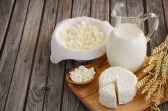 Frische Milchprodukte Milch und Hüttenkäse mit Weizen auf dem rustikalen hölzernen Hintergrund Stockfoto