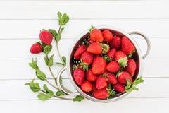 Frische Minze und Erdbeeren im Sieb auf weißem Holztisch Lizenzfreies Stockfoto