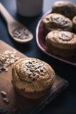 Frische Muffins mit Mischsamen und Schale im Hintergrund stockbild