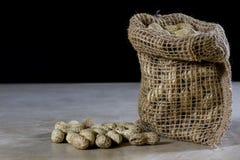 Frische Nüsse in einem Jutefaser bauschen sich auf einem hölzernen Küchentisch Italienische Haselnüsse in der Küche vor Weihnacht Lizenzfreies Stockbild