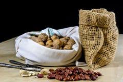 Frische Nüsse in einem Jutefaser bauschen sich auf einem hölzernen Küchentisch Italienische Haselnüsse in der Küche vor Weihnacht Lizenzfreies Stockfoto